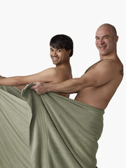 Nude men holding towel open
