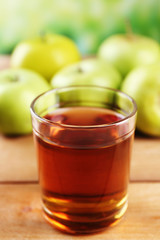 Glass of healthy fresh juice of apples on wooden background