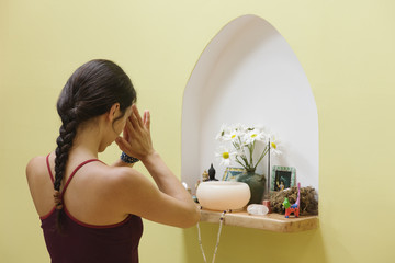 Hispanic woman praying at small shrine