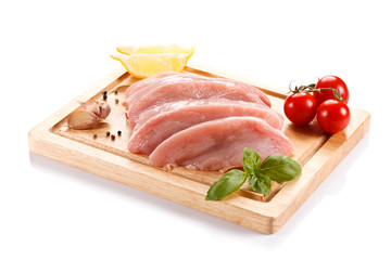 Raw chicken breasts on cutting board on white background