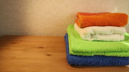 Sliding view of a pile of four colored towels on a table