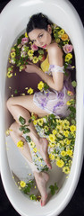Brunet girl in bath with flowers