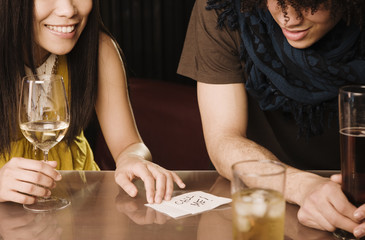 Asian woman giving mixed race man her phone number in nightclub