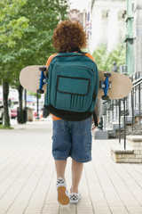 Mixed Race boy carrying skateboard in backpack