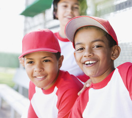 Multi-ethnic boys in baseball uniforms smiling