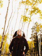 African girl looking up in woods