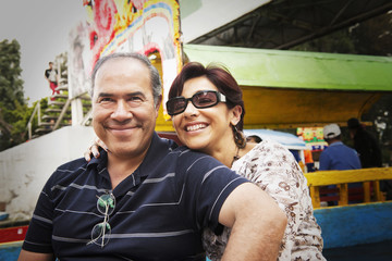 Hispanic couple smiling at amusement park