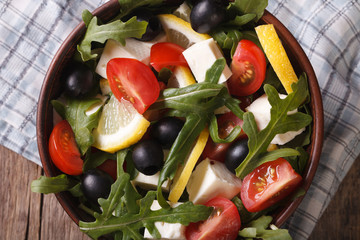 Salad with vegetables, feta and lemon horizontal top view