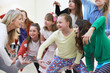 Leinwanddruck Bild - Group Of Children With Teacher Enjoying Drama Class Together