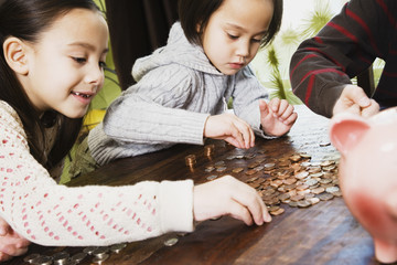 Asian siblings counting coins