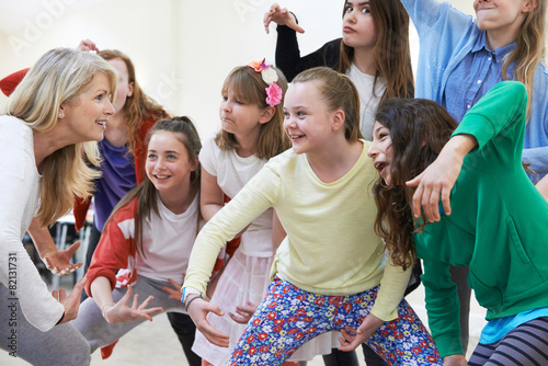 Leinwanddruck Bild Group Of Children With Teacher Enjoying Drama Class Together