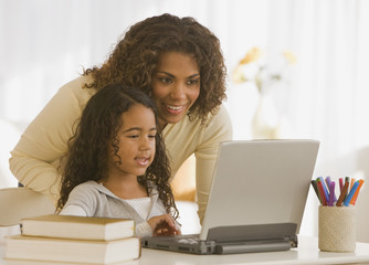 African mother and daughter looking at laptop