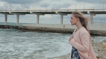 Beautiful girl is sad near the sea