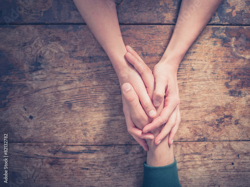 Man and woman holding hands at a table Photo by LoloStock