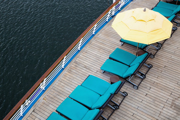 Lounge chairs and beach umbrella on cruise ship deck