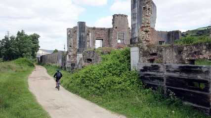 bike riding and motocross on a country road, old house in ruins