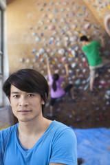 Chinese man smiling in rock climbing gym