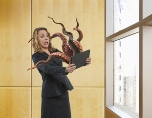 Octopus attacking business woman from digital tablet