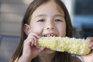 Asian girl eating corn on the cob