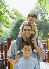 Hispanic father playing with sons at playground