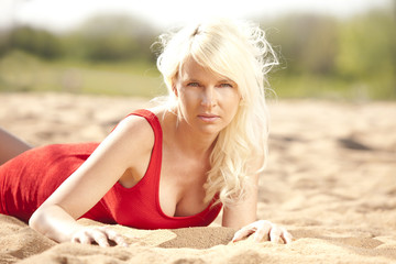 Junge hübsche Frau mit rotem Kleid am Strand