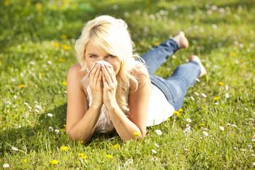 Junge hübsche Frau liegt auf blühender Wiese mit Taschentuch