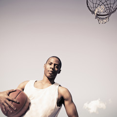 African American man holding basketball on court