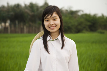 Asian woman in front of field