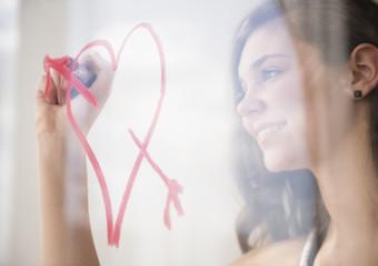 Hispanic girl drawing heart with arrow on window