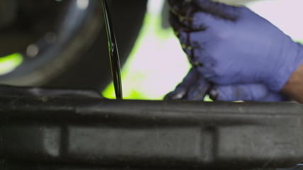 Car mechanic draining oil in slow motion