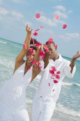 Multi-ethnic couple throwing flower petals in air