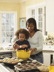 African mother and daughter baking cupcakes