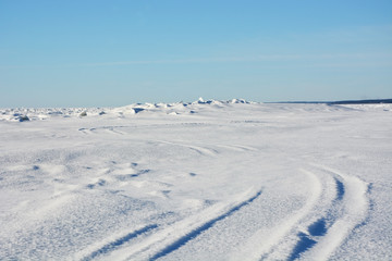 Frozen sea landscape at sunny day with sky tracks
