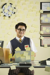 Asian businessman with sticky notes all over wall and desk