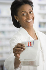 African female pharmacist handing over prescription