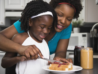 African mother helping daughter make sandwich