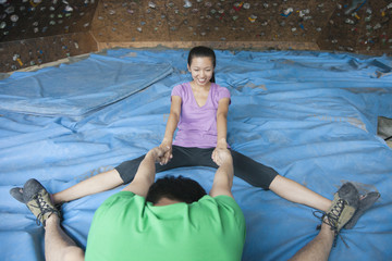 Chinese couple stretching in rock climbing gym