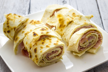 Roll of piadina with ham and cheese