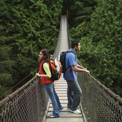 Indian couple wearing backpacks on footbridge