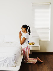 African woman praying at bedside