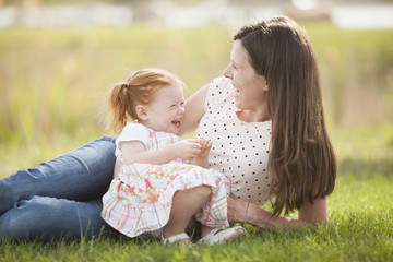 Caucasian mother and baby relaxing in grass