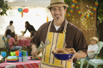 Hispanic man holding food at barbecue