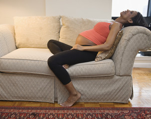Pregnant Hispanic woman sitting on sofa
