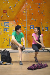 Chinese couple tying shoes in rock climbing gym