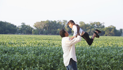 Hispanic father and daughter playing in crop field