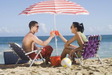 Hispanic couple relaxing at beach