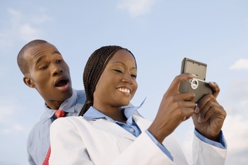 African businesspeople looking at cell phone