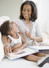 African grandmother looking a photo album with granddaughter