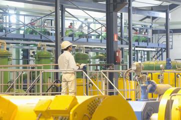 Hispanic worker checking machinery