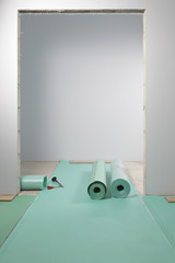 Rolls of underlay, or sub-flooring material, and a partly installed laminate floor